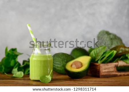 Avocado base home made green smoothies with vegetable leafy greens in a jar standing on a kitchen table, front view #1298311714