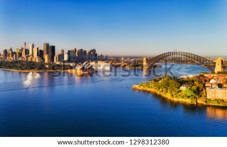 Aerial view over Sydney harbour waters towards city CBD landmarks on waterfront around Sydney Harbour and Circular Quay. #1298312380