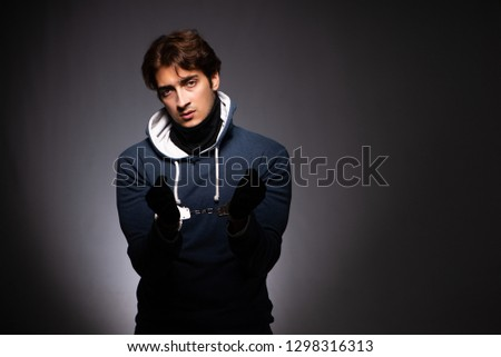 Young gangster in hood on grey background  #1298316313