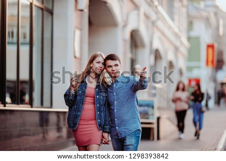 Concept of love relationships man and woman. Lovely couple walking in the big city, hugging, kissing and enjoying each other. eat ice cream and have fun from front #1298393842
