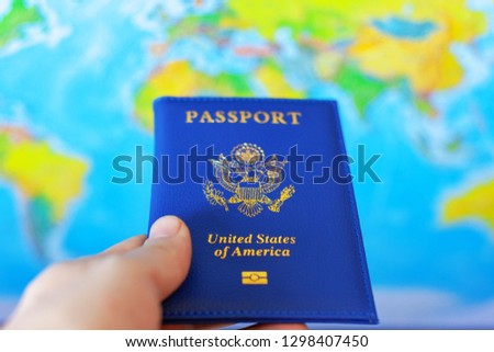 US passport in hand on world map background #1298407450