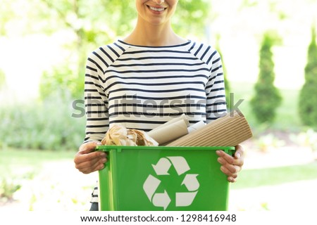 Green box with a recycling sign filled with paper held by a smiling woman #1298416948