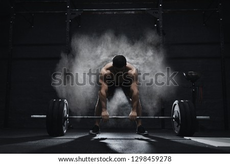 Crossfit athlete preparing to lift heavy barbell in a cloud of dust at the gym. Barbell magnesia protection.  #1298459278