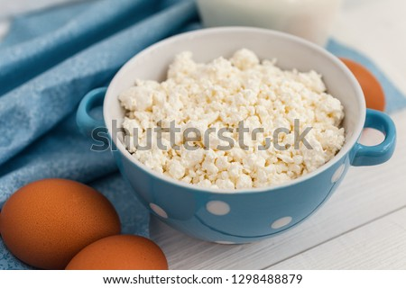 Organic farming cottage cheese in a blue bowl, eggs and milk #1298488879