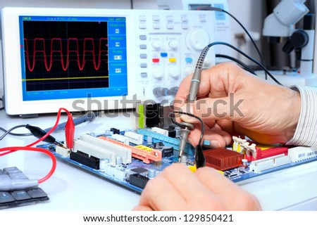 Tech tests electronic equipment in service centre #129850421