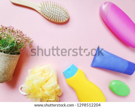Pink spa cosmetics background. Yellow shampoo bottle, pink hair balm, purple body cream, green soap bar, bath sponge, wooden comb and flowers. Flat lay beauty photo. Free space for text #1298512204