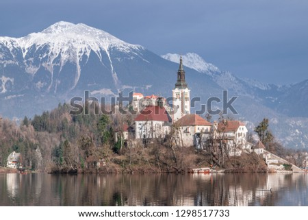 Church on an island in the middle of lake Bled on a snowy mounta #1298517733