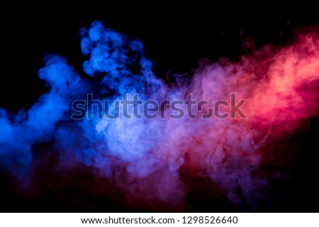 Beautiful horizontal column of smoke in the neon bright light of blue pink and orange on a black background exhaled out of the vape. Nice pattern for printing and backdrop of colored waves. #1298526640