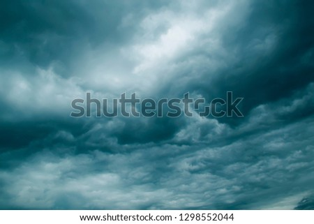Background of dark clouds before a thunder-storm. Dramatic Storm Clouds. Dark blue stormy cloudy sky natural photo background. Water surface. Cloudy sky full of deep grey clouds. Storm is coming.
