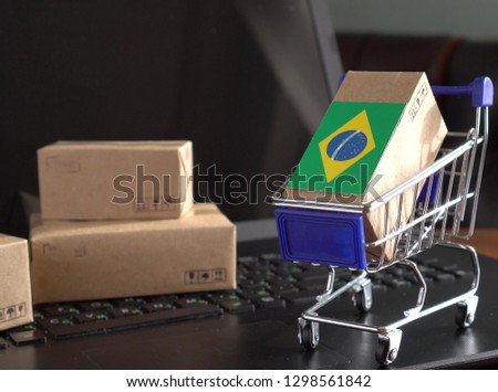 Parcel Boxes with a flag of Brazil in a shopping cart on a laptop keyboard. Export and import markets for goods #1298561842