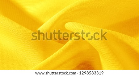 texture background pattern yellow silk fabric. This silk organza has a gentle open weave. Use this luxurious fabric for anything from your design for special occasions to creating your projects. #1298583319