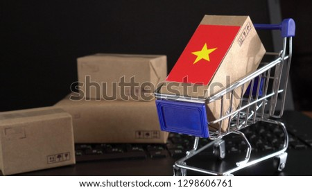 Parcel Boxes with a flag of Vietnam in a shopping cart on a laptop keyboard. International Trade in Goods and Services by Country  #1298606761