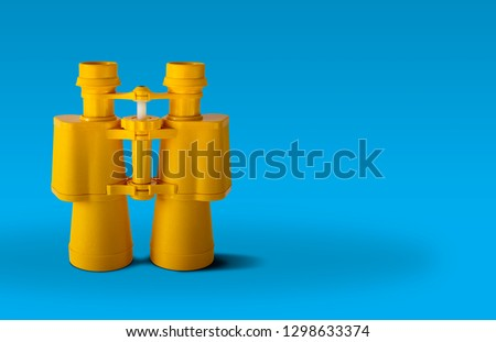 Yellow binoculars isolated on blue background Royalty-Free Stock Photo #1298633374