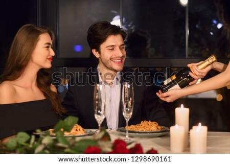young couple having dinner in restaurant, choosing wine #1298690161