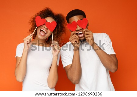 Lovers blinded by their big love.. Young cheerful african-american couple in love holding red hearts over eyes and smiling, orange background #1298690236