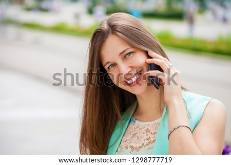 Beautiful young brunette woman calling by phone, summer street outdoors #1298777719