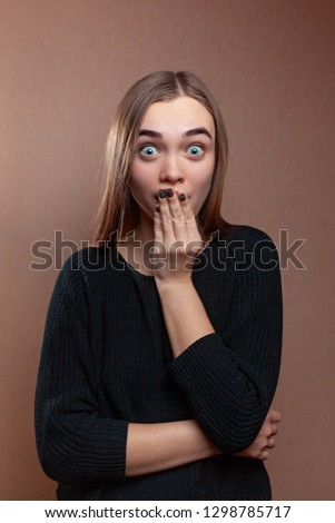 the girl looks carefully at the frame folded hands near the face in a black sweater on a beige background #1298785717