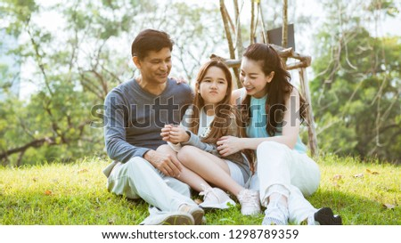 Happy parents and daughter having fun in the park #1298789359