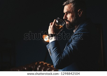 Degustation, tasting. Man with beard holds glass of brandy. Tasting and degustation concept. Bearded businessman in elegant suit with glass of whiskey. Sommelier tastes expensive drink. #1298842504