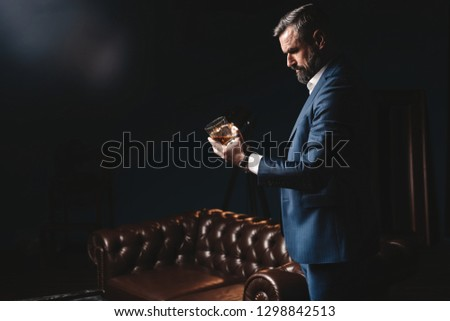 Degustation, tasting. Man with beard holds glass of brandy. Tasting and degustation concept. Bearded businessman in elegant suit with glass of whiskey. Sommelier tastes expensive drink. #1298842513