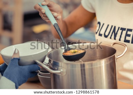 Time for dinner. Close up of a ladle being in use while serving the soup #1298861578