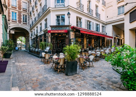 Cozy street near Boulevard San-German with tables of cafe  in Paris, France. Architecture and landmark of Paris. Paris cityscape #1298888524
