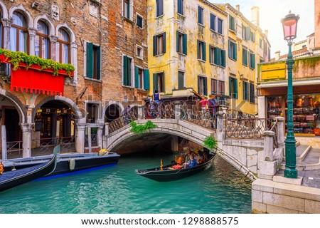 Narrow canal with gondola and bridge in Venice, Italy. Architecture and landmark of Venice. Cozy cityscape of Venice. #1298888575