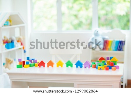 Kids bedroom with white desk and educational toy blocks. Colorful block toys for young children. Nursery room or day care. Kindergarten or preschool class for boy or girl. #1299082864