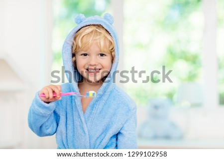 Child brushing teeth. Kids tooth brush and paste. Little baby in blue bath robe or towel brushing his teeth in white bathroom with window on sunny morning. Dental hygiene and heath for children. #1299102958