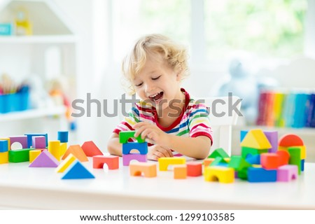 Kid playing with colorful toy blocks. Little baby building tower of block toys. Educational and creative toys and games for young children. Baby in white bedroom with rainbow bricks. Child at home. #1299103585