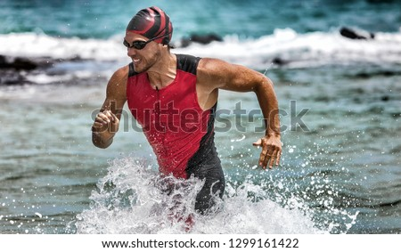 Triathlon swimming man running out of water during ironman race. Male triathlete finishing swim time competition. Fit athlete swimmer sprinting determined out of water in professional tri suit. #1299161422