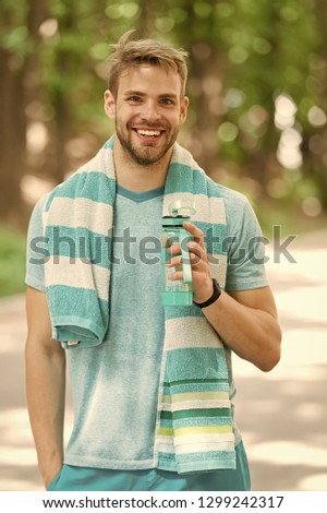 Man with athletic appearance holds bottle with water. Sport and healthy lifestyle concept. Man athlete in sporty clothes training outdoor. Athlete drink water after training at stadium on sunny day. #1299242317