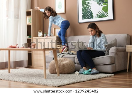 Busy mother with naughty daughter working at home #1299245482