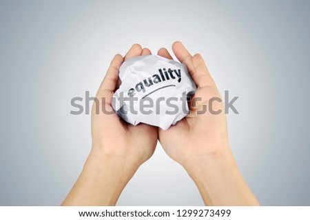 Human hands holding crumpled paper with Equality message over white background #1299273499