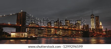 New York City panoramic view of Brooklyn Bridge, East River and Manhattan at sunset with lights and reflections.