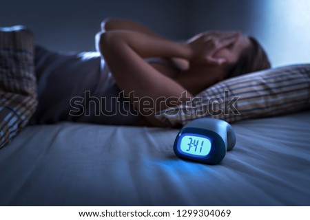 Sleepless woman suffering from insomnia, sleep apnea or stress. Tired and exhausted lady. Headache or migraine. Awake in the middle of the night. Frustrated person with problem. Alarm clock with time. #1299304069