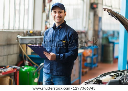 Portrait of a mechanic at work in his garage #1299366943