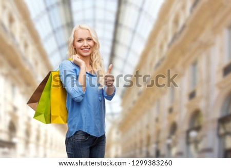 sale and people - woman with colorful shopping bags over mall background showing thumbs up #1299383260