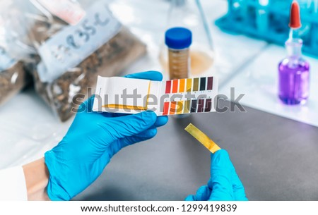 Laboratory Soil Analysis. Female scientist in white coat measuring PH of soil sample with litmus strips. Agrochemical examination of soil. #1299419839