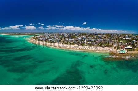 Aerial drone panoramic image of ocean waves on a busy Kings beach, Caloundra, Queensland, Australia #1299425992
