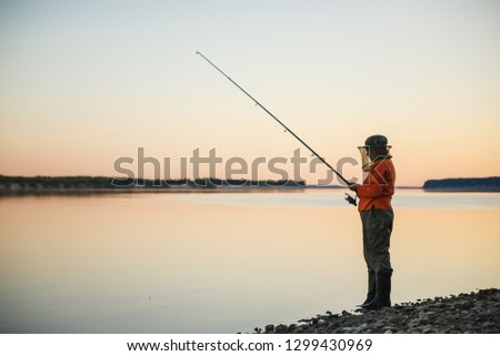 Young woman in mosquito net fishing with fishing rod in the evening. #1299430969