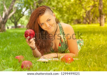 pretty smiling happy girl in green dress reading book and lying on the grass #1299499021