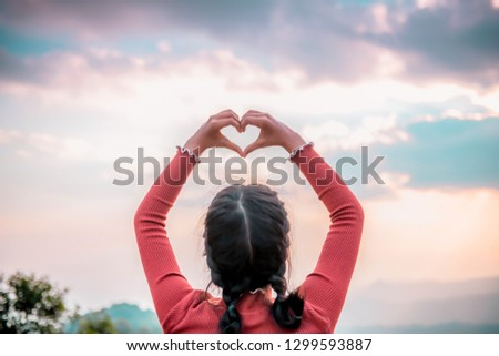 Women hands in the form of love and sunshine in the beautiful sky, the day of love, hands in the heart of love, love concept, heart-shaped hand gesture #1299593887