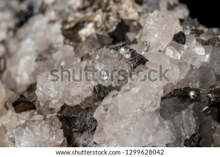 Macro mineral stone Stibnite quartz on a black background close up #1299628042