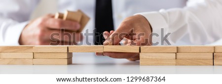 Wide view image of businessman making a bridge of wooden pegs in a conceptual image of business merger and challenge. #1299687364