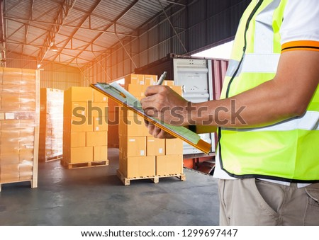 warehouse staff are holding a clipboard with inventory the shipment cardboard boxes on a pallet. #1299697447