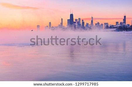 The polar vortex storms over the Chicago skyline. Mist carries off a frozen Lake Michigan during a colorful sunrise.