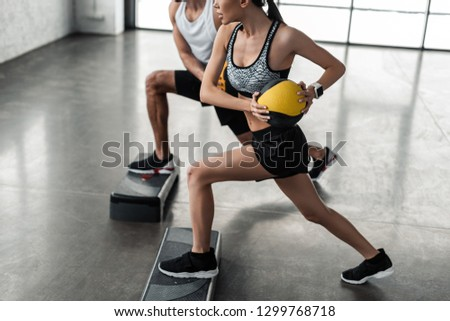 cropped shot of sportive young couple holding medicine balls and exercising on step platforms in gym #1299768718