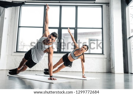 full length view of athletic young couple doing side plank exercise on yoga mats in gym #1299772684