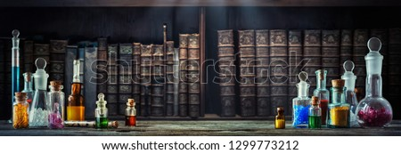 Vintage medications in small bottles on wood desk and old book background. Old medical, chemistry and pharmacy history concept background. Retro style. Royalty-Free Stock Photo #1299773212